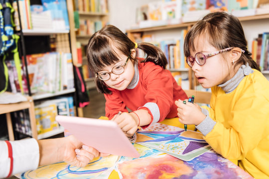 Dark-haired preschool girls with Down syndrome having drawing class