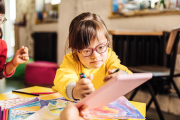 Cute dark-haired girl with Down syndrome wearing glasses