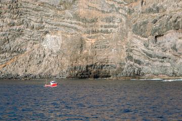 Fototapeta Mała, czerwona łódka na tle wielkiej skały obraz