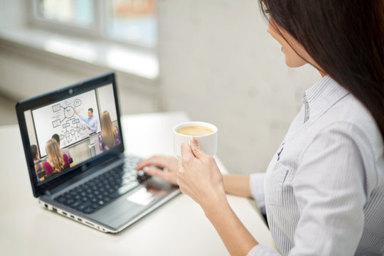 business, education and technology concept - close up of woman drinking coffee and watching webinar on laptop computer at office