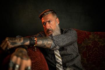 Porträt eines bärtigen Geschäftsmannes auf einer Couch vor dunklem Hintergrund