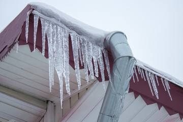 Icicle on the roof of the pipe,Building covered with big icicles,Icicles hang from the roof, vertical, ice stalactite hanging from roof
