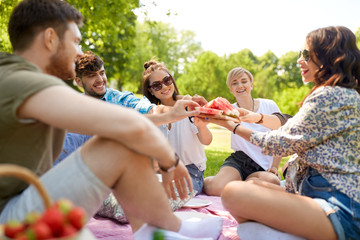 friendship, leisure and food concept - group of happy friends sharing watermelon at picnic in summer park Wall mural