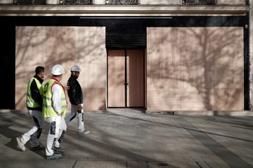 """Workmen walk past a shop which has been boarded with wood panels against possible damage in the event of clashes on the eve of the """"yellow vests"""" protest against higher fuel prices, on the Champs-Elysees Avenue in Paris"""