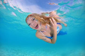 Funny golden-haired mermaid swims underwater surface in blue water, Indian Ocean, Maldives