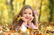 Kleines Mädchen liegt lächelnd auf einem Waldboden