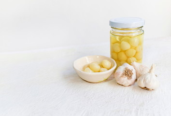 Pickled garlic in a glass jar and Pickled garlic in a bowl with garlic on a white wooden table and white background, image with copy space for text or image.