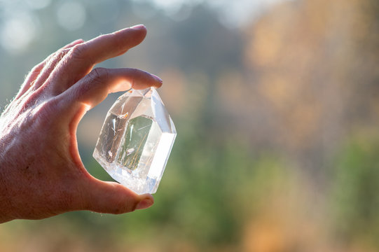 A Hand holding a transparent crystal quartz with the sun hitting the gemstone and a blurry background