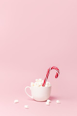 Christmas New Year drink, white mug with marshmallows and Candy Cane on pink background Flat Lay copy space. Winter traditional drink food. Festive decor, celebration Xmas holiday 2019