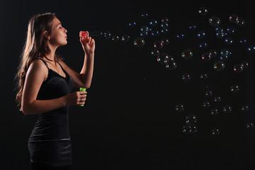 girl in dress blowing bubbles