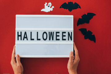 Woman's hands holding 'Halloween' sign