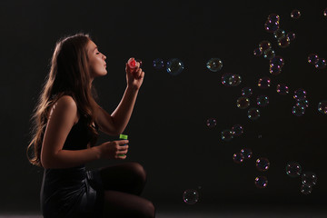 girl in dress blowing bubbles