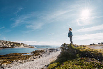 Finland, Lapland, woman standing at the coast in backlight