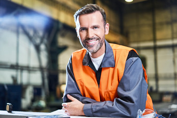 Portrait of smiling man in factory wearing safety vest
