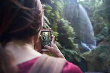 Woman taking picture of waterfall with smartphone in forest