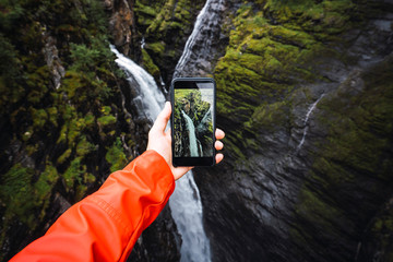 Person taking smartphone picture of a waterfall, Lapland, Norway