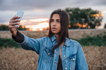Portrait of young woman taking selfie with smartphone in nature at sunset