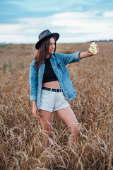 Young woman wearing hat and denim jacket taking selfie with camera in a corn field