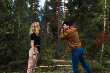 Finland, Lapland, man taking picture of woman in rural landscape