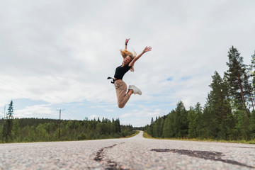 Finland, Lapland, exuberant young woman jumping in rural landscape