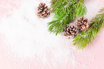 Christmas background, green pine branches, cones decorated with snow on snowy pink background. Creative composition with border and copy space design top view. New Year's, holiday, decoration