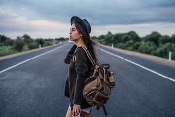 Portrait of hitchhiking young woman with backpack and beverage on lane