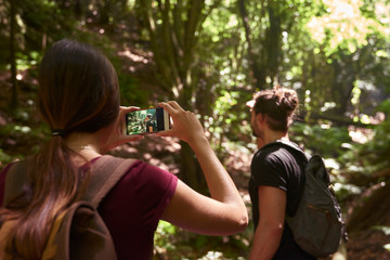 Spain, Canary Islands, La Palma, woman taking a cell phone picture of her boyfriend in a forest