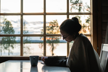Finland, Lapland, young woman sitting at the window at a lake looking in diary