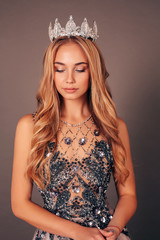 beautiful woman with long blond hair in luxurious evening dress with crown on her head