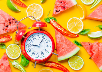 Above view at Watermelon and Chili pepper with lemons near alarm clock on yellow background