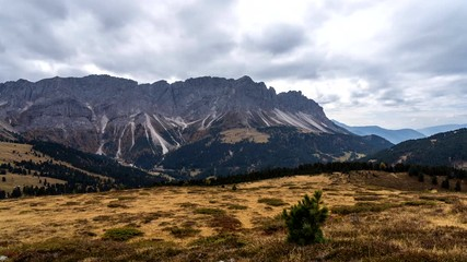 Wall Mural - Colorful scenic time-lapse shot of majestic Dolomites mountains in Italian Alps. Landscape timelapse footage of colorful trees and rocky mountains in the the Italian Dolomites during autumn time.