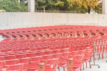 Foto op Aluminium Theater Line of raised orchestra level seats from public outdoor performing art venue in Chicago. Fall foliage color in background
