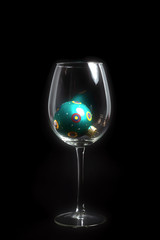 Christmas decoration wine glass on black background with glass ball