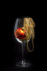Christmas decoration wine glass on black background with glass ball and golden perls