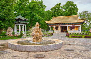 view on green park with stone fountain and traditional chinese buddhist temple