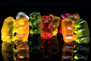 Sweet, delicious gummy bears in small groups, dancing, talking party conceptual image on black shiny surface.
