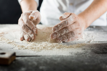 Male chef hands knead the dough with flour on the kitchen table