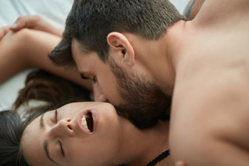 passionate couple Man and girl making love in bed.
