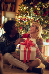Happy man and woman exchanging Christmas presents .