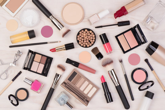 Makeup cosmetics such as eyeshadows, lipstick, mascara and makeup accessories on white, wooden background, top view
