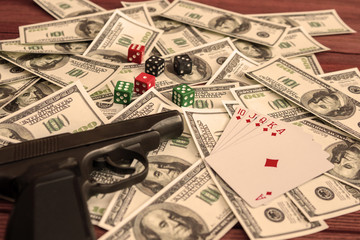gun, dice, cards, American dollar bills. gambling, risk, excitement, danger.