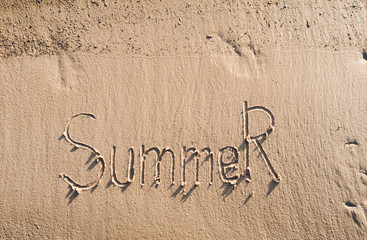 The word summer is written on the wet sand. The inscription is made by hand. Vacation concept.