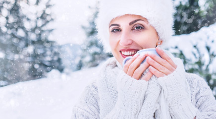 Smiling woman in cozy knitwear and fur hat with cup of hot drink in winter forest medium shot. Winter fashion concept.