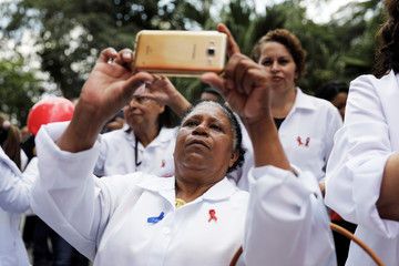 Nurses take pictures of red balloons released ahead of World AIDS Day in Sao Paulo