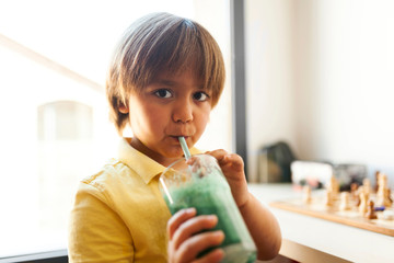 Portrait of cute boy drinking smoothie with straw at home