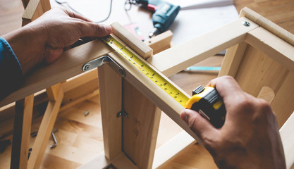 Man assembly wooden furniture,fixing or repairing house with tape measures