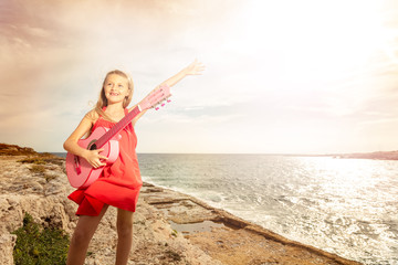 Happy teenage girl playing guitar at the seaside