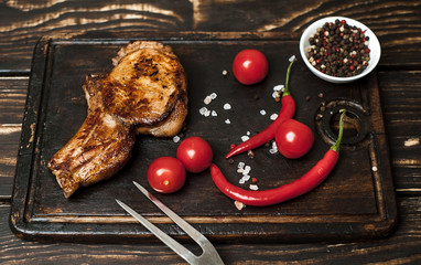 Grilled New York steak with salt and pepper on a dark wooden background