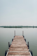 small and lonely pier of the lake in a summer day
