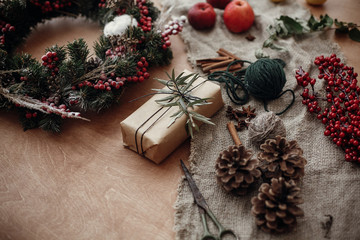 Rustic Christmas wreath and stylish craft gift box with green branch at fir, red berries,pine cones,rope, cinnamon, scissors on rustic wood. Atmospheric moody image, happy winter holiday